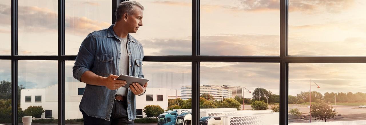 Mężczyzna trzymający tablet stoi przy oknie i spogląda w dół na swoją flotę samochodów ciężarowych