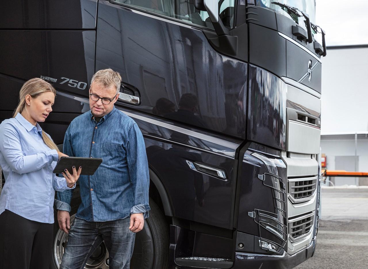 Mężczyzna i kobieta stoją przed samochodem ciężarowym, patrząc na tablet