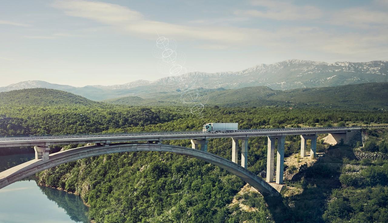 Samochód ciężarowy Volvo z łącznością przejeżdża przez most w odległym miejscu