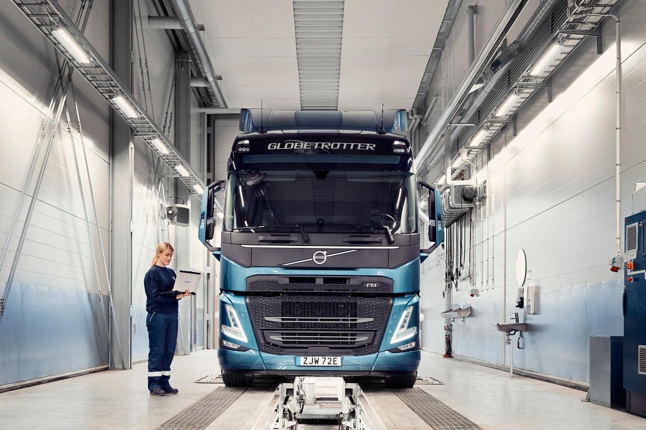 Mechanik serwisu Volvo trzyma komputer, stojąc obok samochodu ciężarowego